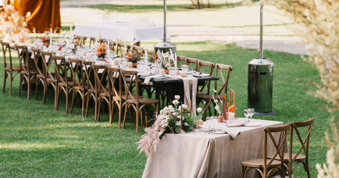 Wedding banquet. Chairs and table for newlyweds decorated with candles, served with cutlery, crockery and covered with tablecloth on green lawn in backyard and long board for guests, panorama